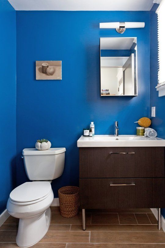 bathroom, blue wall, wooden vanity cabinet white counter top, white toilet, brown floor tiles