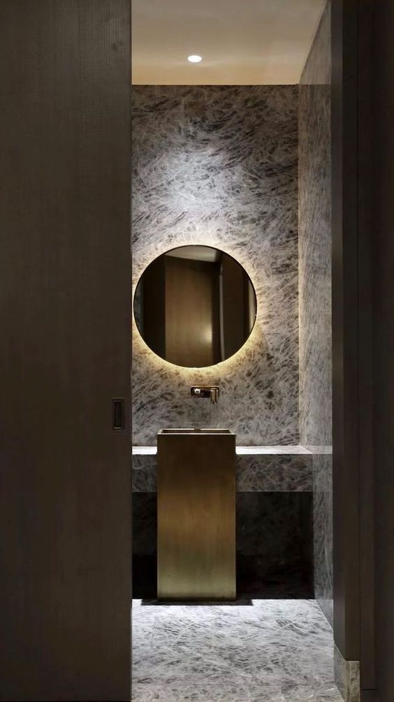 bathroom, grey marble floor and wall, yellow LED from the back of round mirror