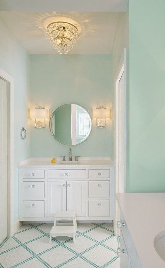 bathroom, soft green wall, white floating vanity cabinet with white top, round mirror, golden chandelier, golden sconces, white green plaid patterned floor
