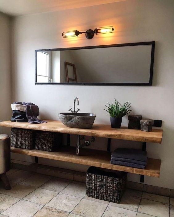 bathroom vanity, brown floor tiles, white wall, wooden floating vanity shelves, grey stone sink, orange sconces