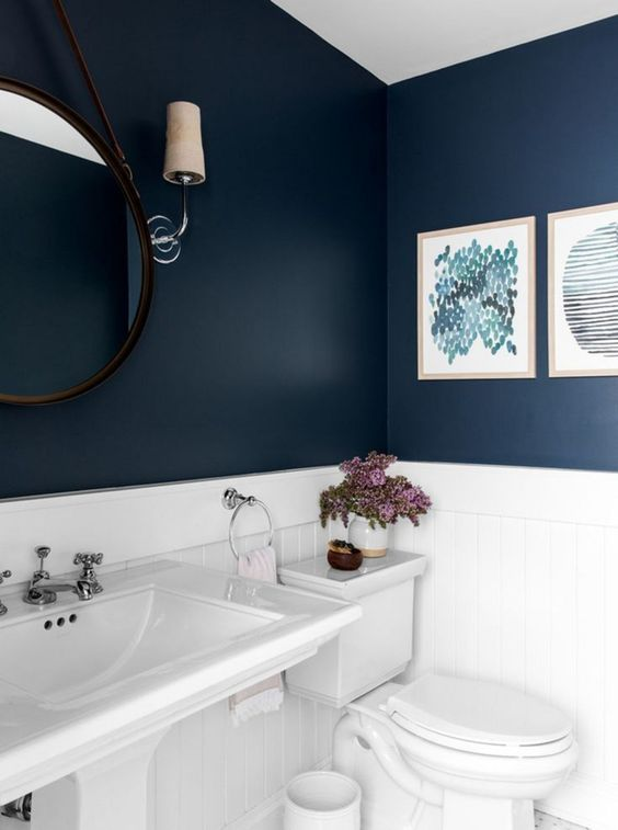 bathroom, white bottom wall, dark blue top wall, white toilet, white sink, round mirror, sconce