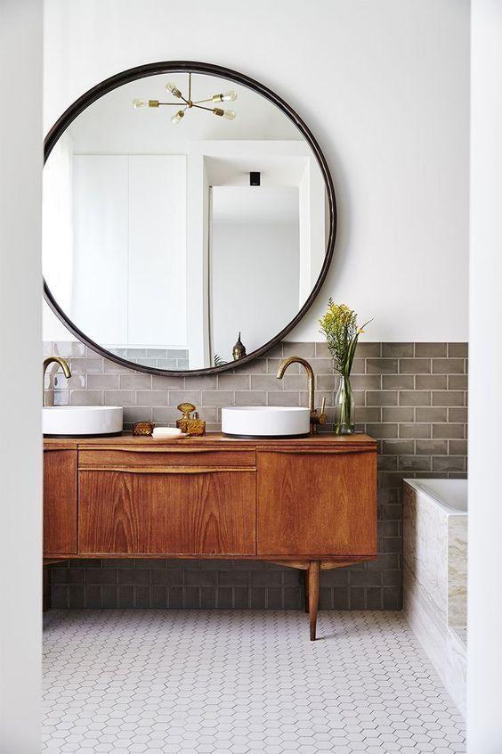 bathroom, white wall, brown subway backsplash, round mirror, wooden cabinet, white sinks, white hexagonal floor tiles, marble tub