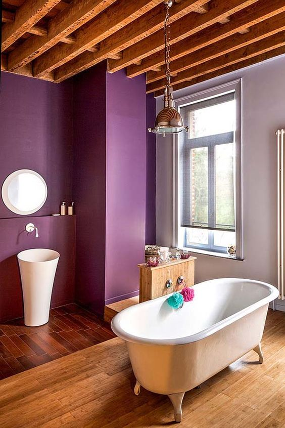 bathroom, wooden floor, purple wall, wooden beamson the ceiling, white sink, white tub
