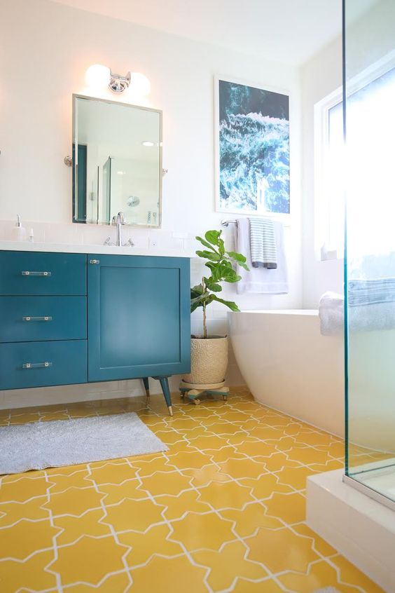 bathroom, yellow patterned floor tiles, white wall, blue wooden counter, white tub, glass shower area