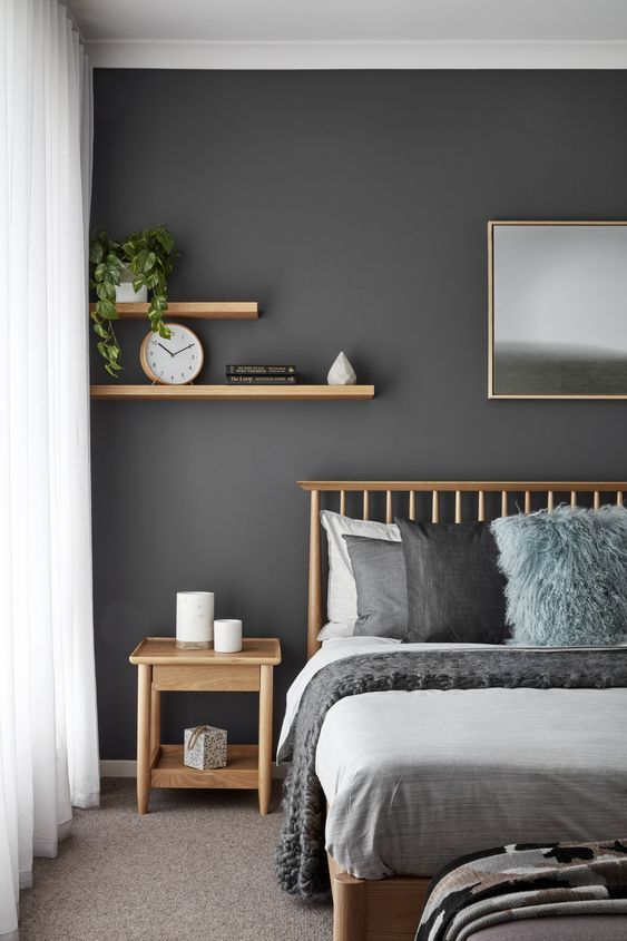 bedroom, grey carpet, grey wall, wooden bed platform, grey bedding, wooden side table, floating wooden shelves