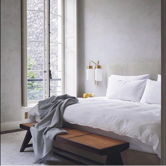 bedroom, grey rug, white wall, tall small glass window, white bed, wooden bench, white sconces