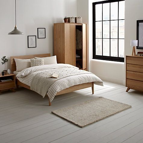bedroom, white wooden floor, white wall, light wooden bed platform, wooden side table, wooden cupboard, wooden cabinet, grey pendant, white rug