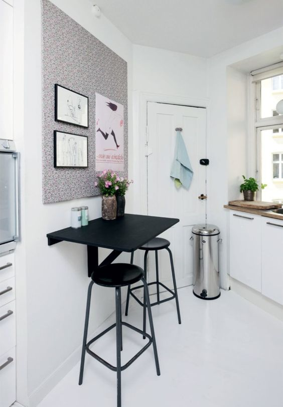black floating table, black stools, white wall, white floor, white cabinet