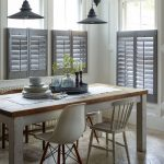Black Hal Window Shutters, White Wall, Wooden Herringbone Floor, Wooden Dining Table, White Wooden Chairs, Black Pendant