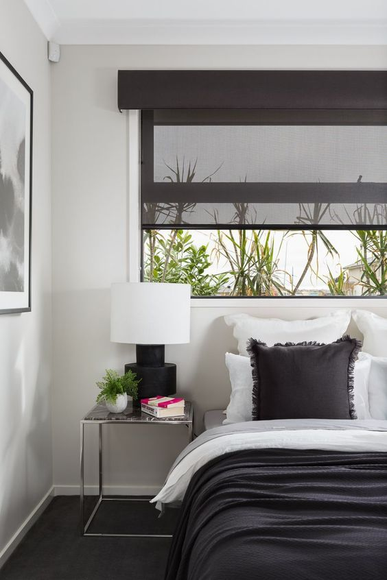 black shade to the window, white wall, wide table, white bed with black cover, black rug