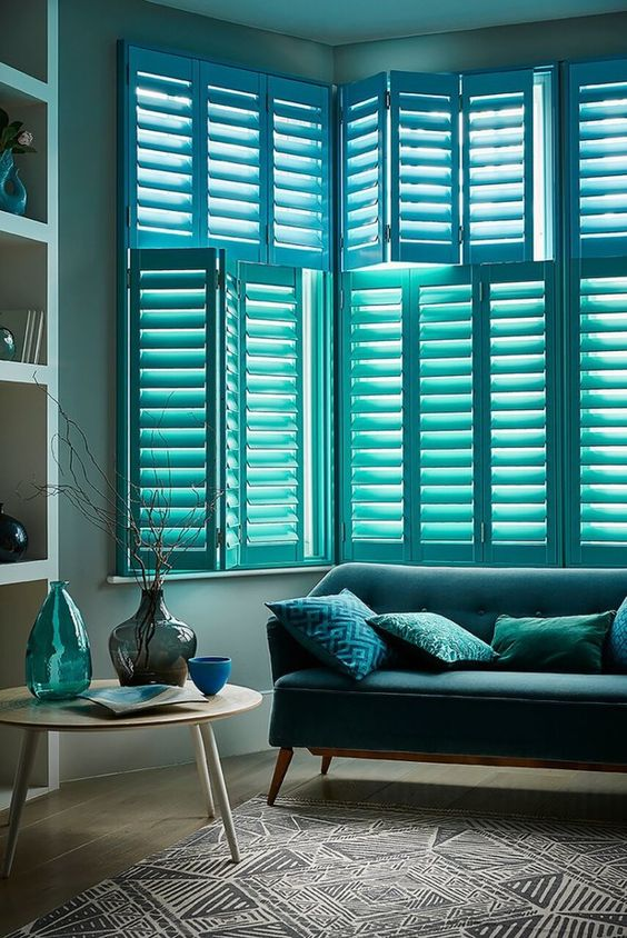 blue green window shutters, grey wall, wooden floor, blue sofa, round coffee table