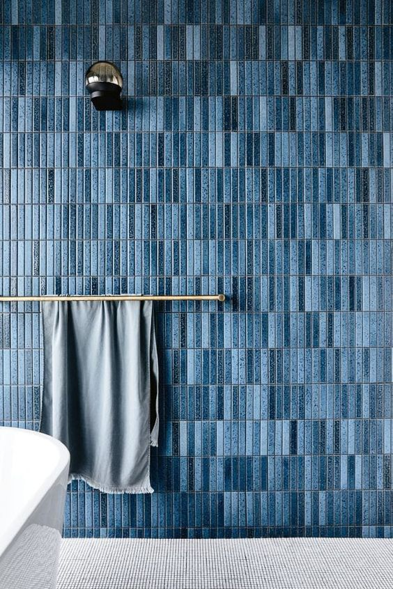 blue thin wall tiles, grey floor, golden towel hanging rack