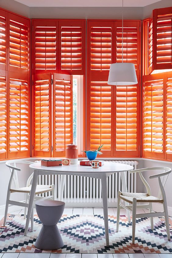 bold orange window shutter, white pendant, white round dining table, white chairs, white wooden floor, white patterned rug