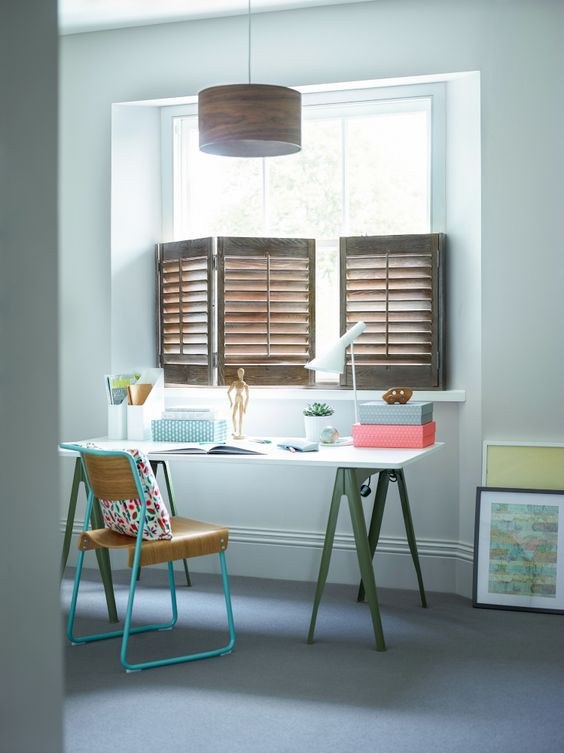 brown wooden half window shutters, white wall, white study table, green feet, green metal chair, wooden pendant