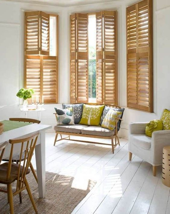 brown wooden window shutters, white wall, white chairs, white wooden floor, wooden sofa with patterned cushion, white dining table, wooden dining chairs