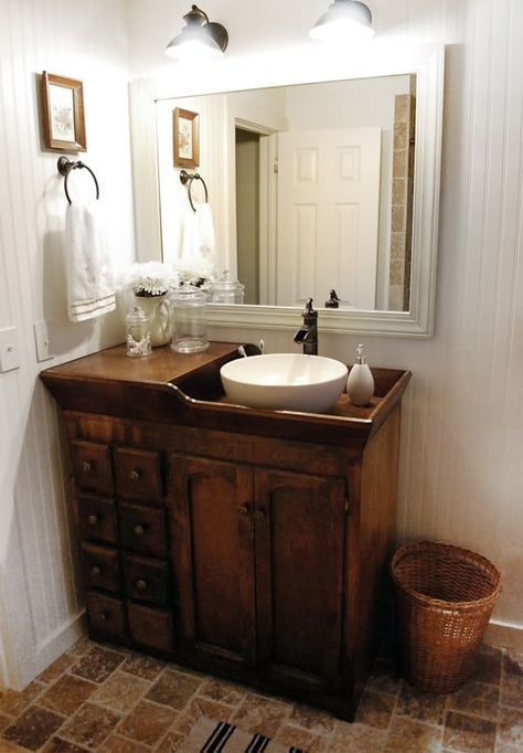 deep dark wooden vanity cabinet, wooden wall, wooden white wooden framed mirror, white bowl sink, brown floor tiles