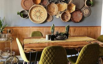 dining room, patterned rug, grey wall, wooden waiscoting, wooden table, green chairs, woden plates wall decoration, chandelier