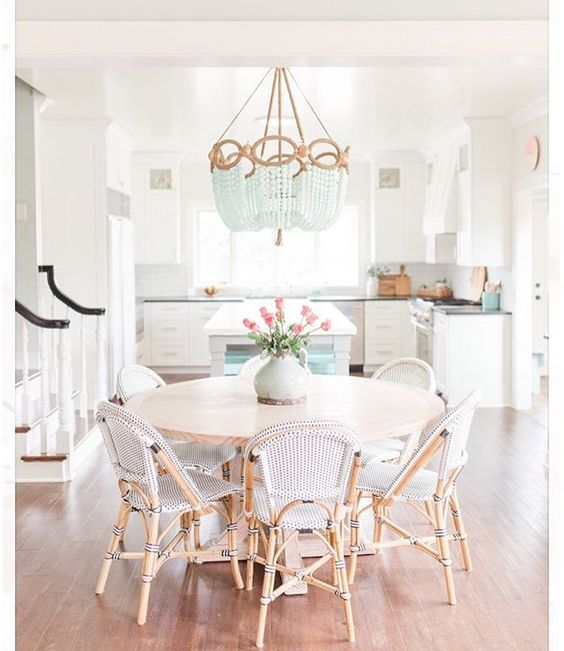 dining set, wooden floor, white wall, wooden round table, rattan chairs, white rattan woven seat, white chandelier