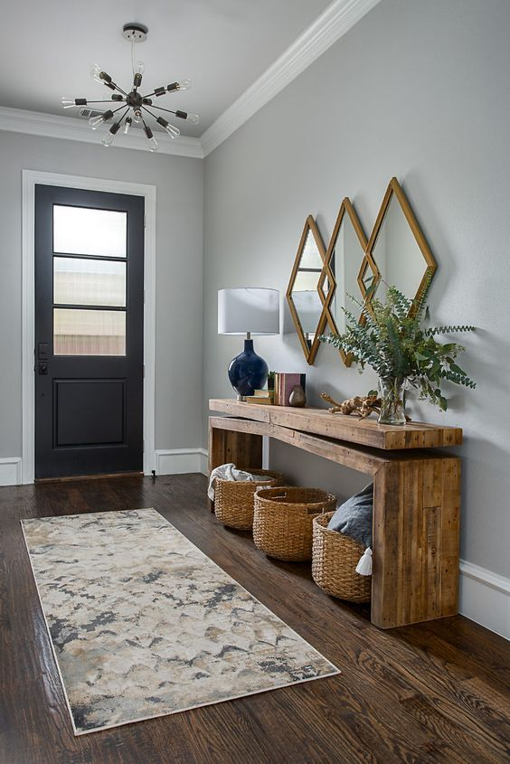 entrance, wooden floor, grey wall, wooden console table, rattan baskets, diamond mirrors, black table lamp, black door, crystal pendant