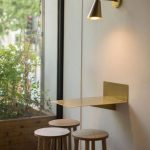 Golden Floating Table, Golden Sconces, Round Wooden Stools, White Wall