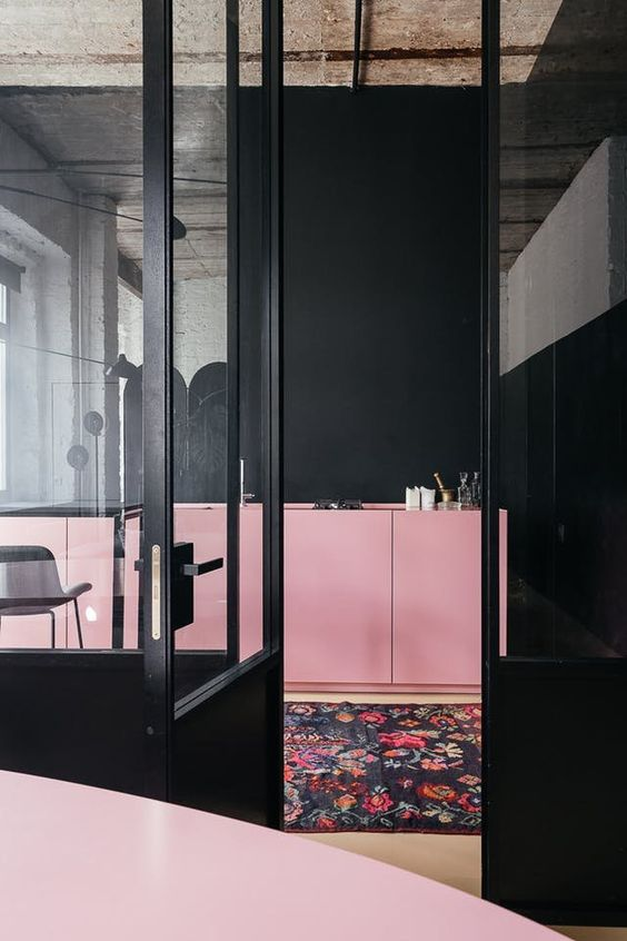 kitchen, black wall, pink bottom cabinet, wooden floor, black rug with flowery patterns