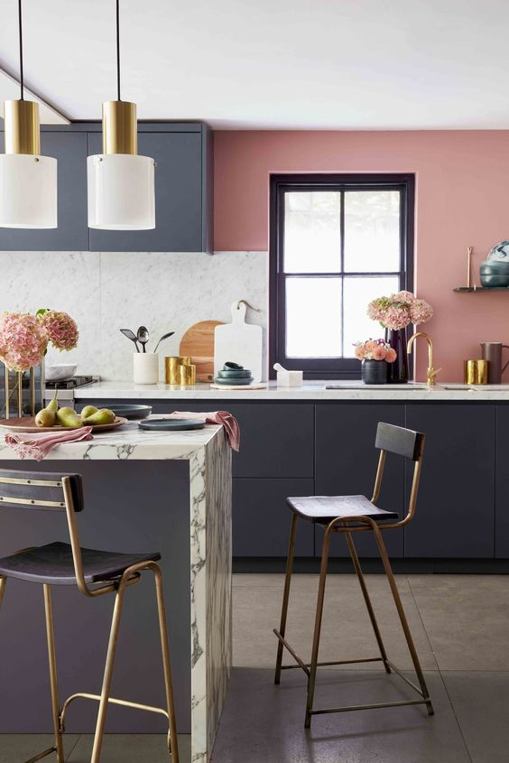 kitchen, dark grey cabinet, marble backsplash, marble island, pink wall, white golden pendant, golden black stools