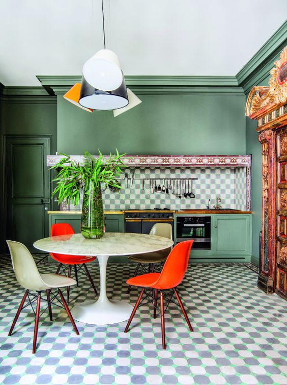 kitchen, green wall, green bottom cabinet, pendant, black white plaid backsplash, white tulip table, white red chairs, geometric floor tiles