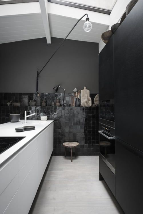 kitchen, grey floor tiles, black cabinet, black wall, black wall tiles, white island, tall floor lamp