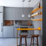 Kitchen, Grey Wall, Grey Cabinet, Grey Counter, Silver Backsplash, Yellow Table, Yellow Floating Shelves, White Pendant, Wooden Stools