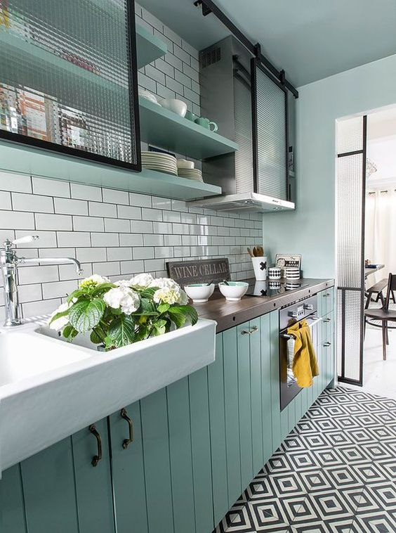 kitchen, mint green bottom cabinet, white subway backsplash, white sink, green shelves, white wall, black and white floor tiles