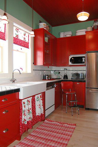 kitchen, wooden floor, red cabinet, green wall, white backsplash, white sink, white pendants