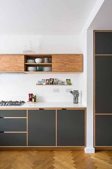 kitchen, wooden floor, white wall, black cabinet with wooden frame, wooden upper cabinet, white counter top