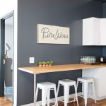 Kitchen, Wooden Floor, Wooden Table, White Stools, White Counter, Black Wall, White Upper Cabinet