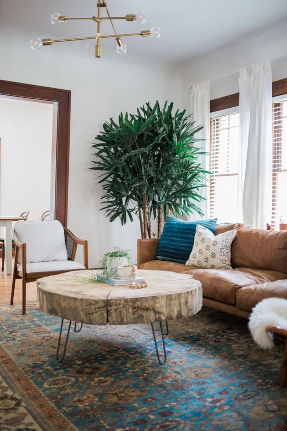 living room, brown leather sofa, white leather cushioned chair, wooden round coffee table, blue patterned rug, modern chandelier
