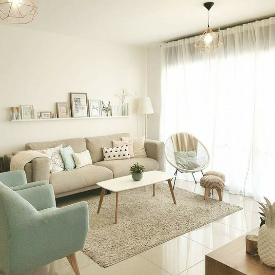 living room, white floor, white wall, off white sofa, soft blue chair, beige rug, beige coffee table, floating shelves
