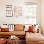Living Room, White Wall, White Floor, Brown Leather Sofa, Patterned Rug, Rattan Ottoman, Brown Leather Ottoman