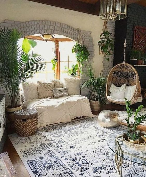living room, wooden floor, white blue rug, white wall, dark wall, window seat with white cover and pillows, rattan chair with white cushions, glass round coffee table