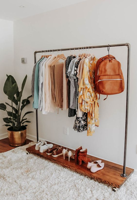 metal rod rack, wooden board, wooden floor, white rug, white wall