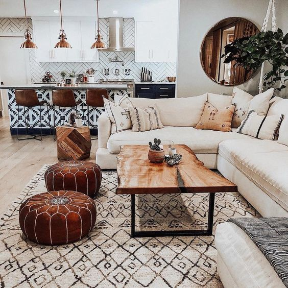 open living room, white sofa, white patterned rug, leather ottoman, patterned island, golden pendants, wooden stools