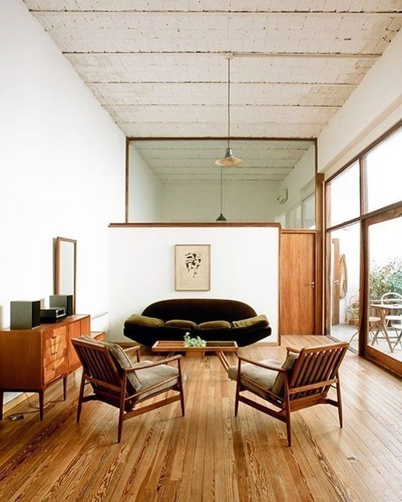 open living room, wooden floor, green velvet sofa, wooden chairs with cushion, wooden cabinet, pendant, glass widow, glass door