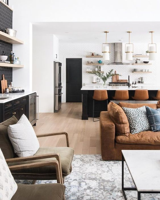 open living room, wooden floor, white wall, black island with white top, balck cabinet, black subway wall tiles, brown sofa, brown chairs, white coffee table