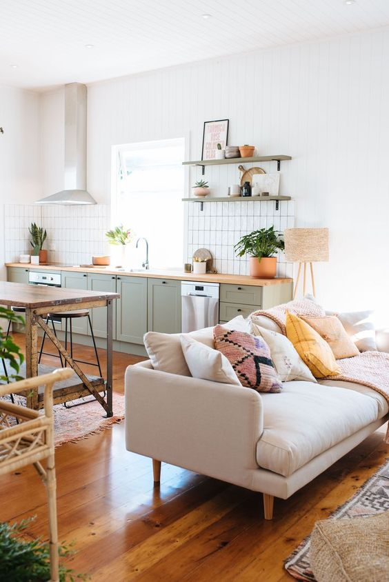open living room, wooden floor, white wall, mint green bottom cabinet, floating shelves, wooden table