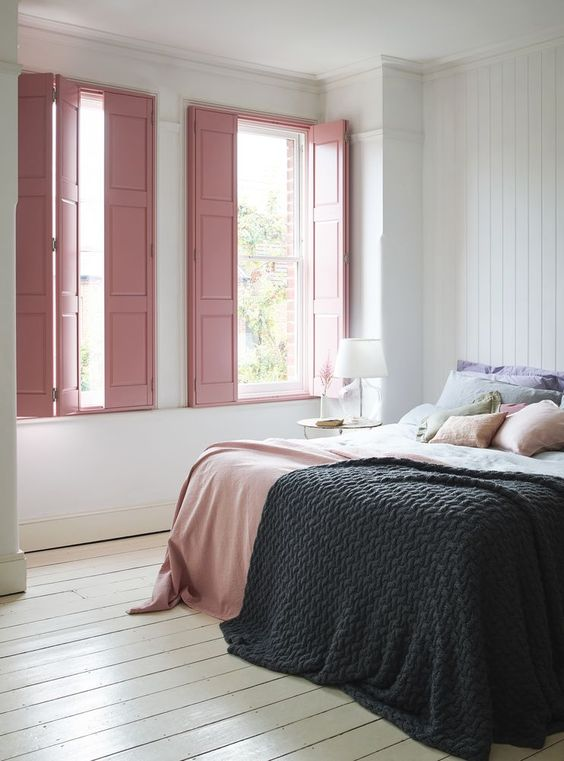 pink wooden window shutters, white wall, white wooden floor, white wooden accent wall, large bed, golden side table with white table lamp
