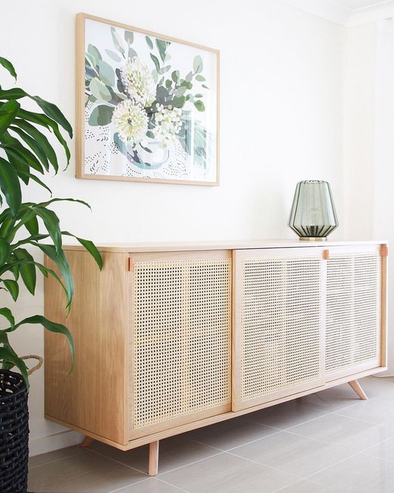 rattan low cabinet, grey floor tiles, white wall, painting