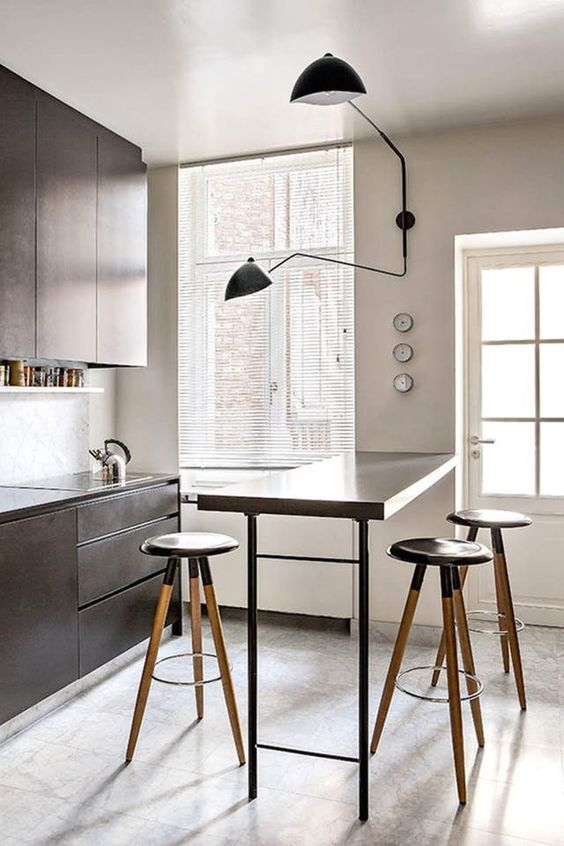 simple kitchen, grey floor tiles, dark brown wooden cabinet and counter, dark brown table, wooden stools, white wall, black sconces