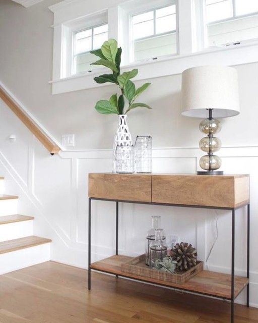 small wooden console with thin black lines, white pendant, white wall, white wainscoting, wooden floor
