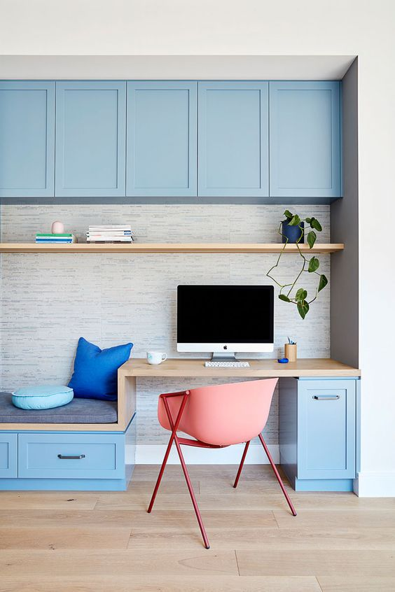 study, wooden floor, white wall, blue upper cabinet, grey background, wooden shelves, wooden built in table and bench, blue bottom cabinet, pink chair