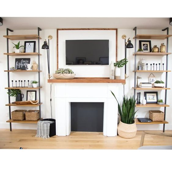 wall mounted shelves, wooden boards, grey metal support, TV above fireplace, white wall, wooden board, black sconces