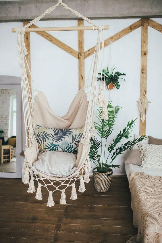 white cloth bohemian hammock chair, wooden floor, white wall, wooden accessories, white bed