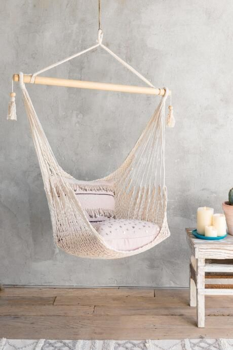 white knitted hammock swing, grey wall, wooden floor, wooden table